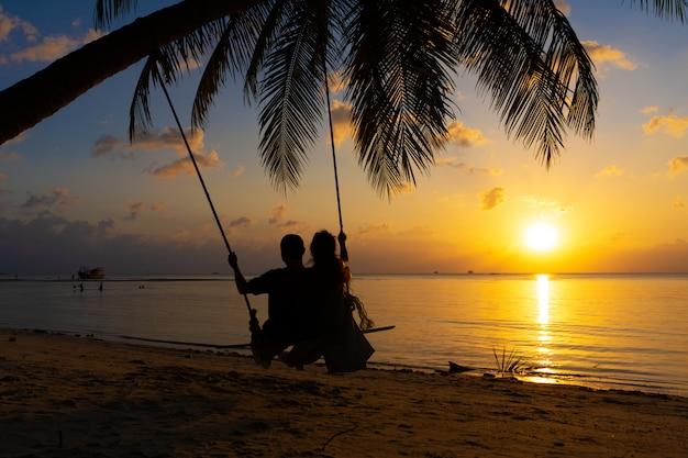 Sylwetki zakochanych spacery na plaży podczas zachodu słońca. jazda na huśtawce przywiązanej do palmy i obserwowanie słońca schodzącego do oceanu