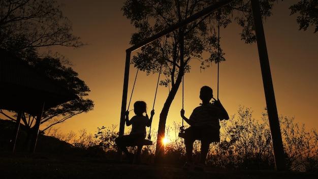 Sylwetkowe dzieci chłopiec i dziewczynka korzystających piękny słoneczny dzień gra tło