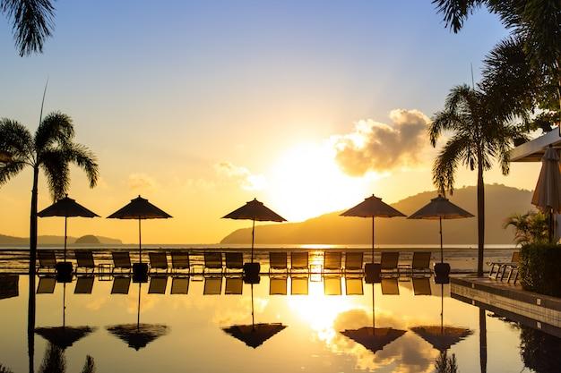 Sylwetkowy obraz, piękny wschód słońca na plaży z łóżkiem i basenem.