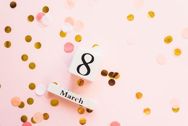 Symbol 8 marca. świąteczny dzień kobiet koncepcja z drewnianym kalendarzem i marca, data 8 na różowym tle z konfetti. miejsce na tekst i reklamę