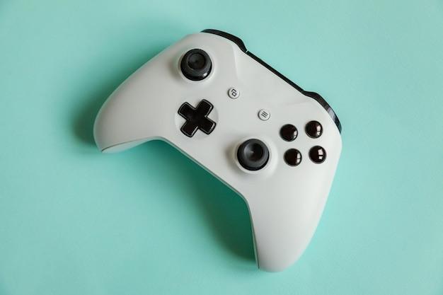 Symbol cyberprzestrzeni. biały joystick gamepad, konsola do gier na pastelowej niebieskiej kolorowej modnej powierzchni. koncepcja konfrontacji kontroli gier komputerowych.