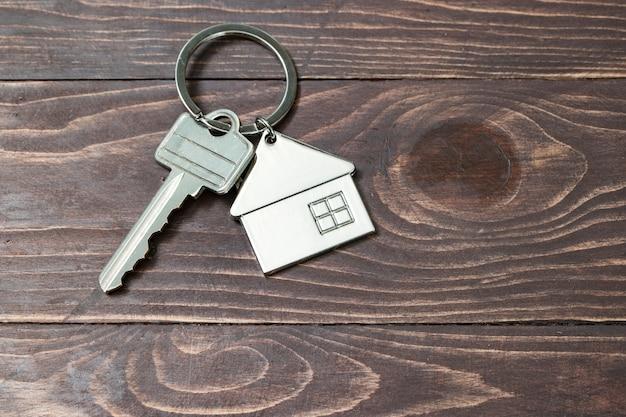 Symbol dom z srebro kluczem na rocznika drewnianym tle