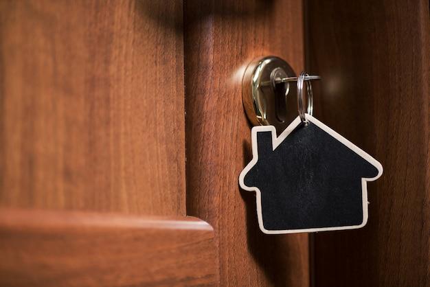 Symbol domu i włóż klucz w dziurkę od klucza na zamkniętych drzwiach