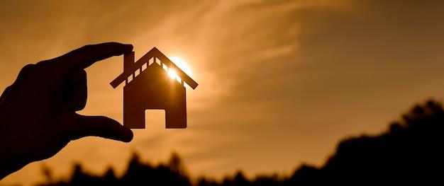 Symbol domu o zachodzie słońca w postaci konturów w kobiecych rękach. zdjęcie wysokiej jakości