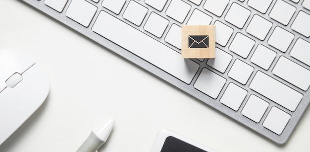 Symbol e-mail na drewnianej kostce. biurko biznesowe