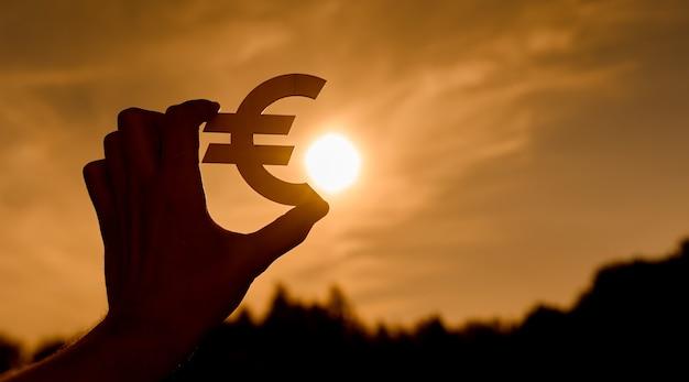Symbol euro w rękach kobiet wyprofilowane o zachodzie słońca. zdjęcie wysokiej jakości