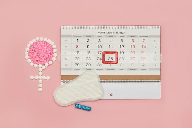 Symbol kobiety wykonany z tabletek i kalendarza miesiączkowego, żeńskich dni okresu lub koncepcji cyklu miesiączkowego
