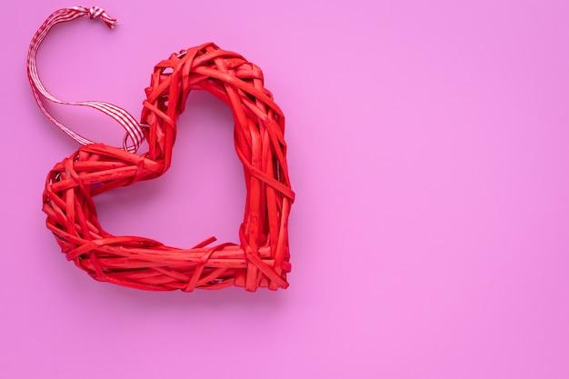 Symbol miłości, romantyczne tło z czerwonym sercem domowej roboty na różowym tle. kopiuj, przestrzeń tekstowa. karta upominkowa na walentynki.
