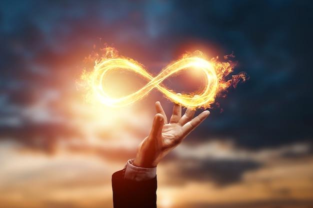 Symbol nieskończoności ognia nad ręką biznesmena