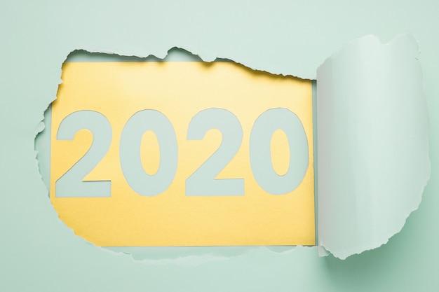 Symbol nowego roku, liczby 2020 wycięte ze złotego niebieskiego papieru tła. torn księga tło dziura miętowy kolor.