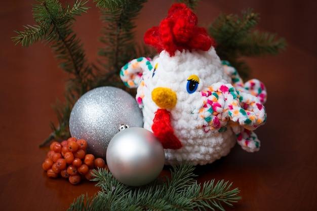 Symbol nowego roku - ręcznie robiony kogut z gałązkami jodły i żurawiną