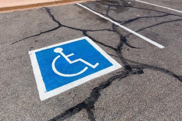 Symbol osoby niepełnosprawnej na miejscu parkingowym.