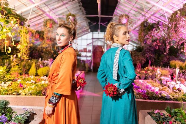Symbol piękna. ładne, poważne kobiety stojące z czerwonymi kwiatami, odwracające głowy do ciebie