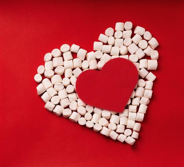Symbol serca wykonany z pianek z czerwoną kartką w kształcie serca w środku na czerwonym tle. widok z góry. flat lay
