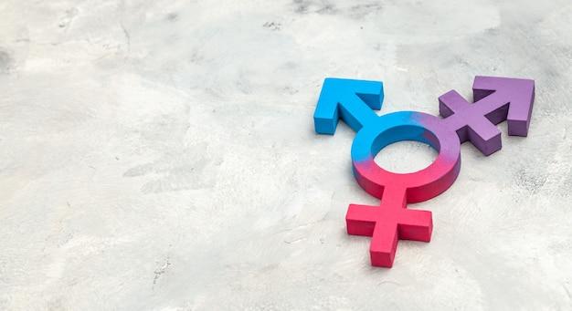 Symbol transpłciowych i symbol płci mężczyzny i kobiety na szarym tle.