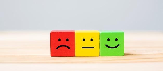 Symbol twarzy emocji na drewnianych klockach