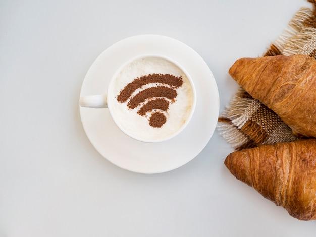 Symbol wifi w filiżance z rogalikami