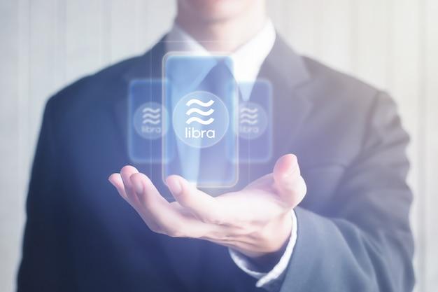 Symbol wirtualnej waluty libra na ekranie trzymał w rękach azjatyckiego mężczyznę biznesu