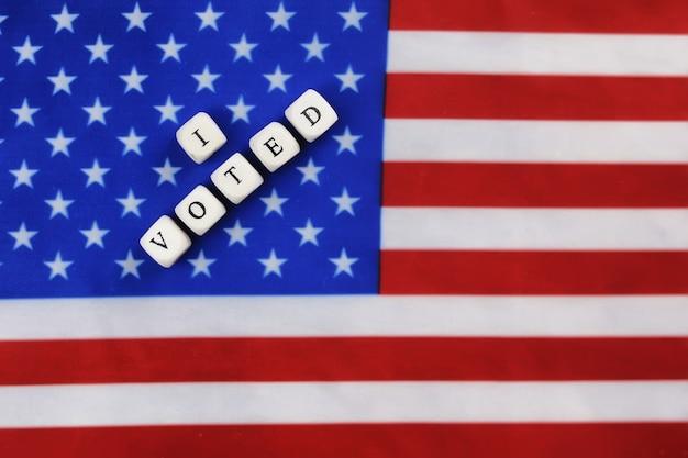 Symbol wyborczy na fladze usa z drewnianymi kostkami z literą