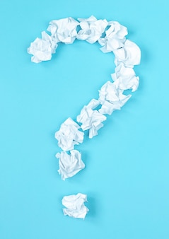 Symbol znaku zapytania ułożone przez zmięty papier kulkowy na niebieskim tle. koncepcja znalezienia pomysłu i rozwiązania problemu.