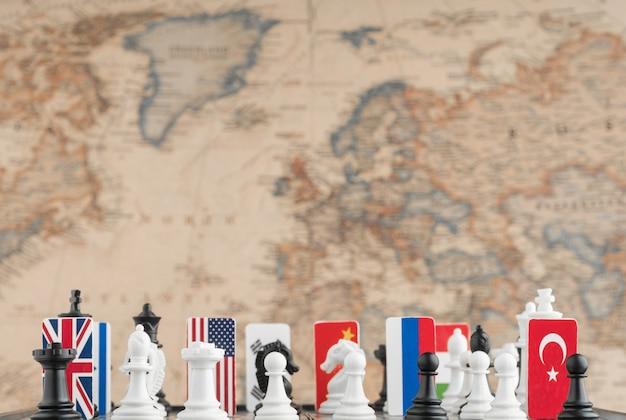 Symbole flag państwowych na szachownicy z cyframi na tle mapy politycznej