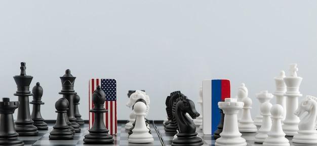 Symbole flagi rosji i stanów zjednoczonych na szachownicy. pojęcie gry politycznej.