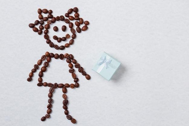 Symboliczna dziewczyna z ziaren kawy i pudełko. na białym tle na białej powierzchni.