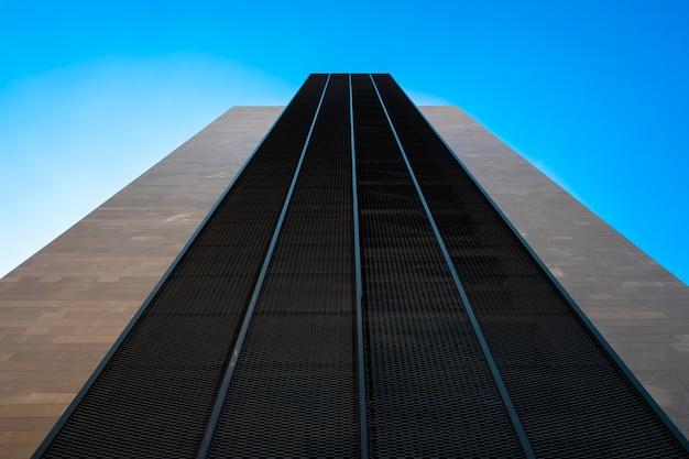 Symboliczny wysoki budynek z perspektywą mocy, minimalistyczna konstrukcja skierowana w stronę błękitnego nieba, symetryczny design dla współczesnych środowisk.