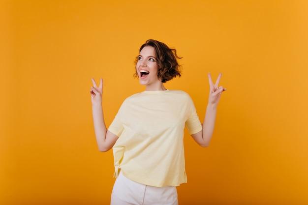 Sympatyczna dziewczyna z tatuażem tańczy z rękami do góry. kryty zdjęcie romantycznej brunetki kobiety wyrażającej szczęście.