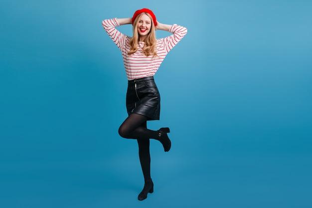 Sympatyczna francuska dziewczyna stojąca na jednej nodze z uśmiechem. beztroski blondynka młoda kobieta tańczy na niebieskiej ścianie.