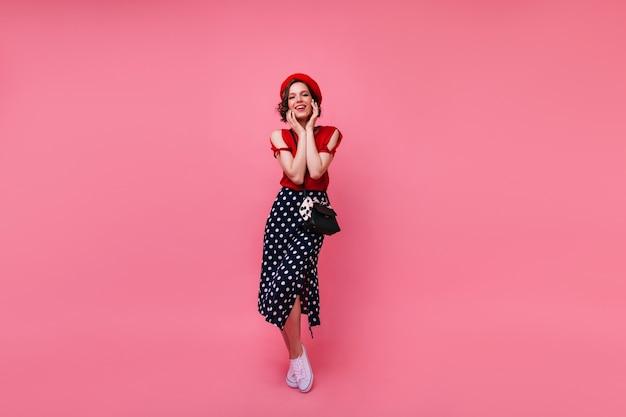 Sympatyczna francuska dziewczyna w białych butach pozuje ze szczerym uśmiechem. kryty ujęcie pełnej długości beztroskiej krótkowłosej kobiety w czerwonym berecie.