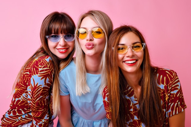 Sympatyczna grupa stylowych dziewczyn uśmiechających się i wysyłających pocałunek, super modne tropikalne ubrania z nadrukiem i kolorowe okulary w stylu lat 90., najlepsi przyjaciele cieszą się razem, różowa ściana