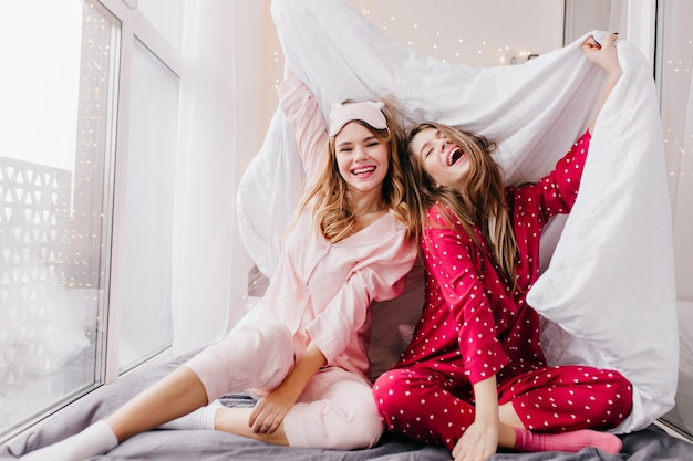 Sympatyczna młoda kobieta ma na sobie różowy kombinezon i uśmiechnięte skarpetki. wewnętrzne zdjęcie roześmianych dziewcząt żartujących podczas pozowania w sypialni.
