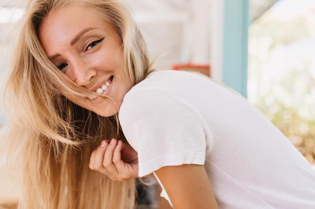 Sympatyczna modelka w codziennych ubraniach, figlarnie patrząc przez ramię. zdjęcie wyrafinowanej blondynki wygłupiającej się podczas domowej sesji zdjęciowej.