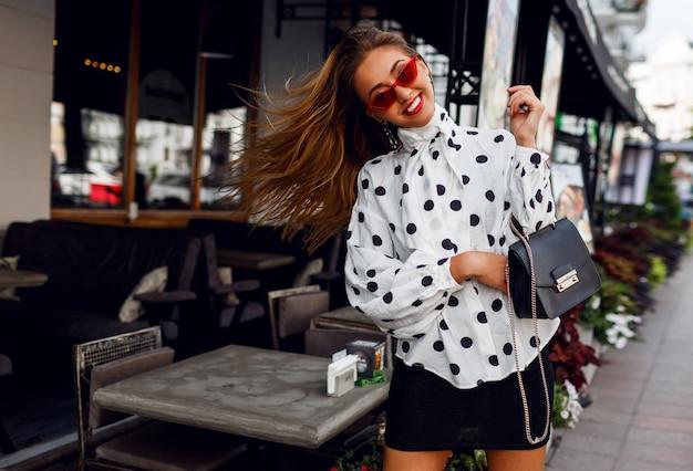 Sympatyczna pewna siebie blond kobieta z długimi fryzurami pozuje na ulicy nad nowoczesną kawiarnią. modny wygląd.