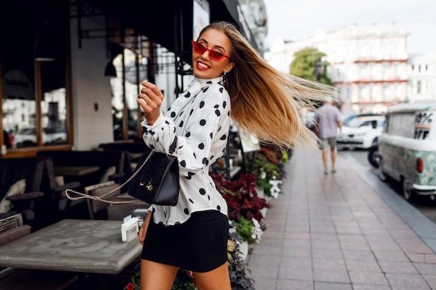 Sympatyczna pewna siebie blond kobieta z długimi fryzurami pozuje na ulicy nad nowoczesną kawiarnią
