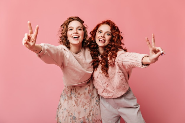 Sympatyczne dziewczyny pokazujące znaki pokoju i uśmiechnięte. studio strzałów dwóch przyjaciół na białym tle na różowym tle.