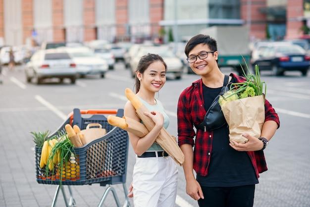 Sympatyczny azjatykci para trzyma papierowe eco torby z organicznie zdrowym jedzeniem w rękach podczas gdy stojący blisko sklepu centrum handlowego.