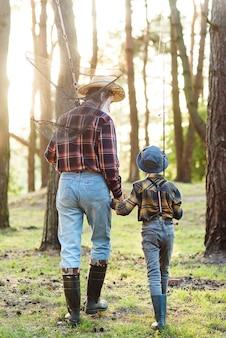 Sympatyczny, pewny siebie, brodaty dziadek w lesie razem ze swoim dziesięcioletnim wnukiem na ryby i rozmawiający o wędkowaniu.
