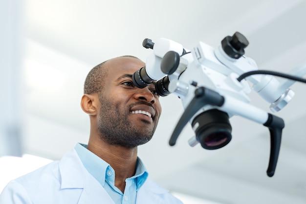 Sympatyczny, wesoły dentysta, uśmiechnięty szeroko i patrząc w soczewkę mikroskopu podczas badania zębów swoich pacjentów