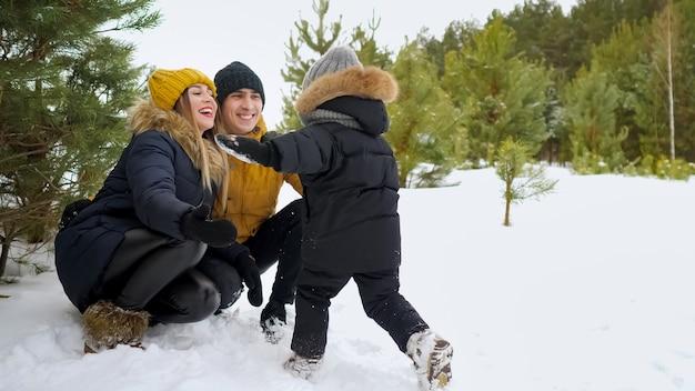 Syn biegnie i przytula rodziców w winter park. razem padają w śnieg. szczęśliwa koncepcja rodziny.