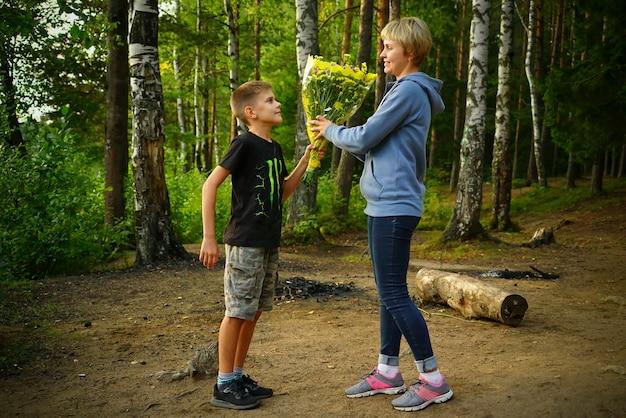 Syn daje kwiaty swojej matce w naturze na jeziorze.