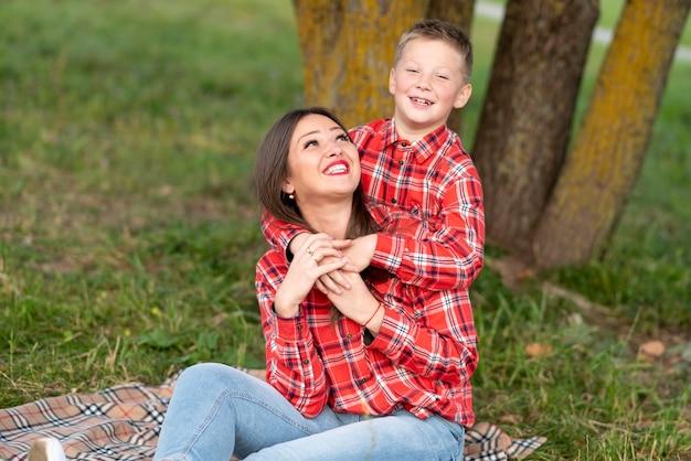 Syn delikatnie przytula mamę w ramiona, oboje uśmiechają się radośnie. w dowolnym celu.