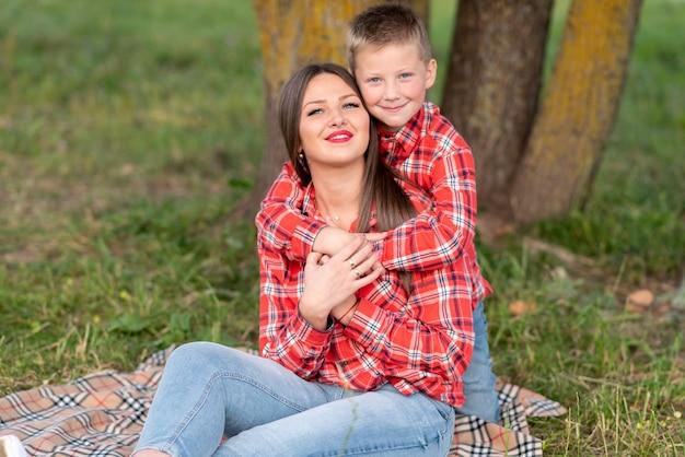 Syn delikatnie przytula ramiona matki, oboje uśmiechając się, siedząc na narzucie w kratkę