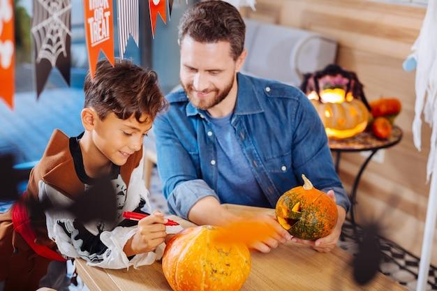 Syn dołącza. kochający brodaty ojciec dołącza do swojego uroczego syna kolorującego dynie na imprezę halloween w domu z rodziną