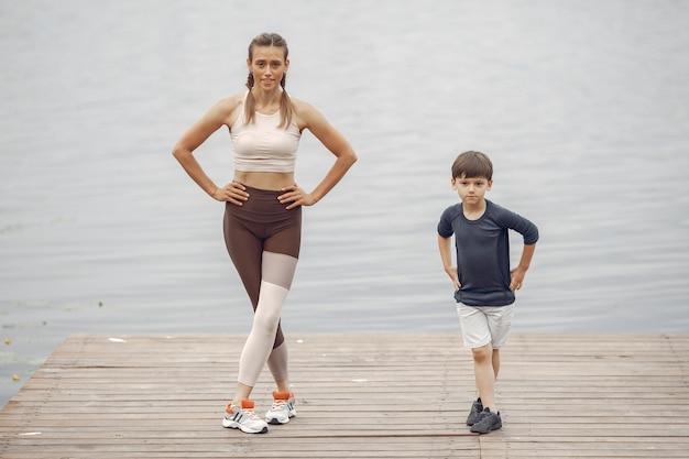 Syn i mama ćwiczą w letnim parku. rodzina nad wodą.