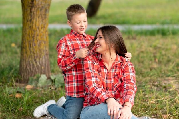 Syn klęczący za matką bawi się jej włosami. w dowolnym celu.