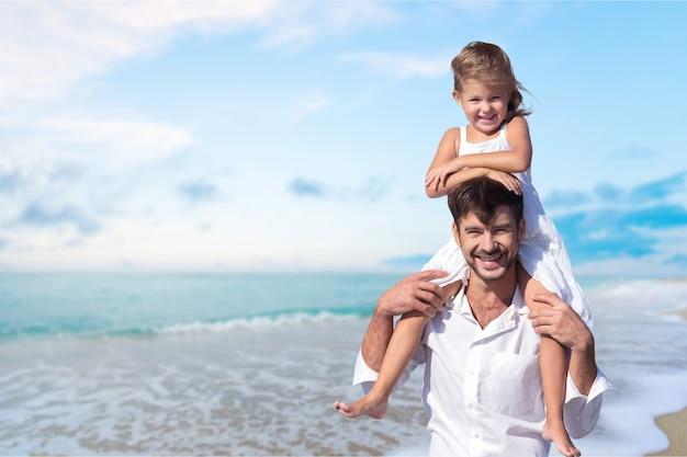 Syn na ramionach ojca na plaży bawi się razem o zachodzie słońca