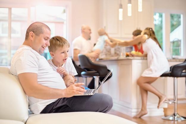 Syn z ojcem siedzi na kanapie, patrząc na laptopa, w kuchni mama przyjaciół i dziecka