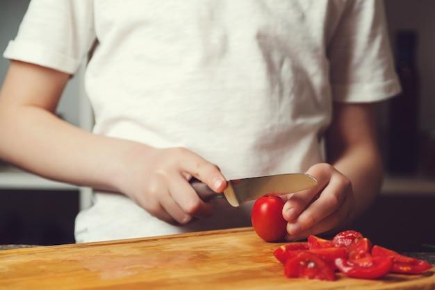 Synek uczy się kroić pomidory. kucharz kroi warzywa na sałatkę na desce do krojenia,